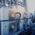 Air conditioner units (HVAC) on a roof of industrial building with blue sky and clouds in the background.
